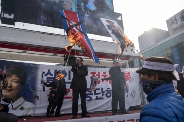 Protesters in Seoul burn a North Korean flag during a rally against the visit by Kim Yong Chol with an eight-member delegation for the Pyeongchang Winter Olympic Games' closing ceremony