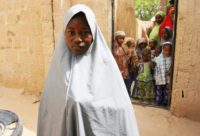 Hassana Mohammed, 13, seen outside her Dapchi home, scaled a fence to escape an alleged Boko Haram attack on her technical college which left more than 100 girls reported missing