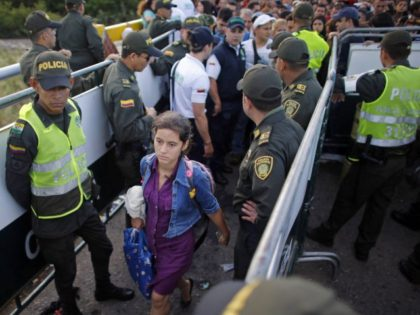 In this July 17, 2016 file photo, police stand guard as a Venezuelan woman crosses into Colombia through the Simon Bolivar bridge linking San Antonio del Tachira, Venezuela, with Cucuta, Colombia. President Juan Manuel Santos announced Thursday, Feb. 8, 2018, that more than 2,000 new officers will be dispatched to …