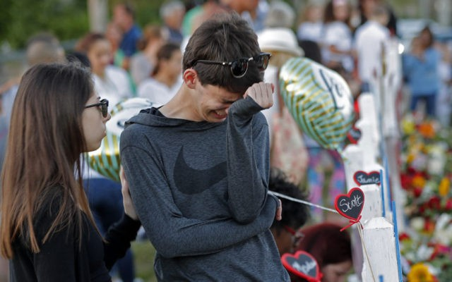 Daniel Bishop, 16, a student at Marjory Stoneman Douglas High School, cries at a makeshift memorial outside the school, in Parkland, Fla., Sunday, Feb. 18, 2018. Nikolas Cruz, a 19-year-old who had been expelled from the school, is being held without bail in the Broward County Jail, accused of 17 …