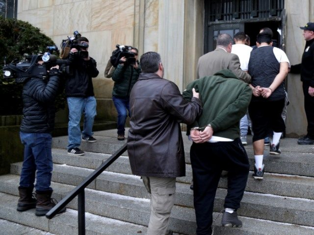 Law Enforcement officers bring MS-13 gang members to court.