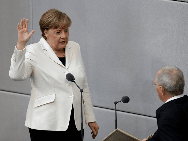 German Chancellor Angela Merkel takes the oath of office in front of Parliament President Wolfgang Schaeuble after Merkel was elected for a fourth term as chancellor in the German parliament Bundestag in Berlin, Germany, Wednesday, March 14, 2018. (AP Photo/Michael Sohn)