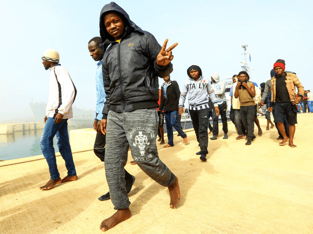 An African migrant flashes the victory gesture after disembarking following his rescue from off the coast of Zawiyah, about 45 kilometres west of the Libyan capital Tripoli, at the dock at the capital's naval base on March 10, 2018. / AFP PHOTO / MAHMUD TURKIA (Photo credit should read MAHMUD TURKIA/AFP/Getty Images)