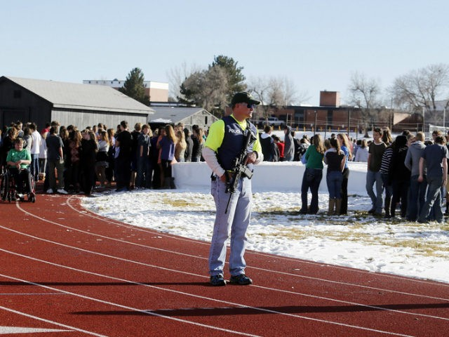 Sheriffs deputies stand guard over students after they were evacuated to the track and football field at Arapahoe High School in Centennial, Colo., on Friday, Dec. 13, 2013, where a student shot at least one other student at a Colorado high school Friday before he apparently killed himself, authorities said. …