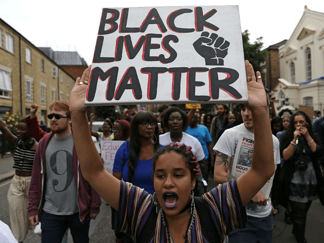 A women holds up a placard with the slogan 'Black Lives Matter' as people march in Brixton, south London to protest against police brutality in the US, on July 9, 2016, after two recent incidents where black men have been shot and killed by police officers.