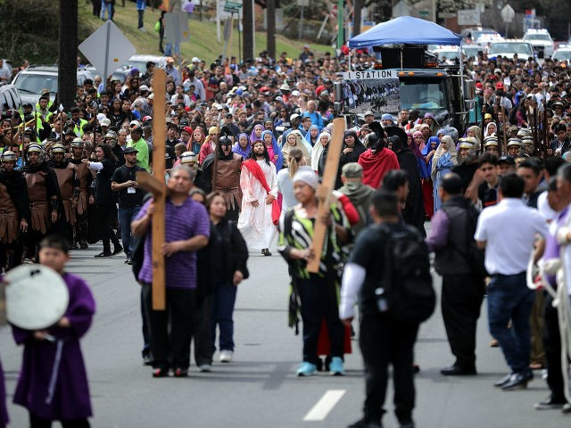 Thousands of people follows actors as they portray Jesus Christ and Roman centurions during a traditional Via Crucis, or Way of the Cross, procession on the Christian Good Friday holiday March 30, 2018 in Takoma Park, Maryland. The re-enactment of the crucifixion of Jesus drew several thousand area Catholics and …