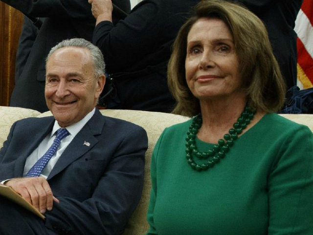 Chuck Schumer sits with Nancy Pelosi, both smiling.