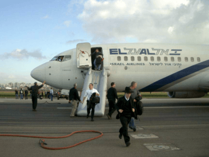 Passengers and crew members flee away of an El Al aircraft at Ben Gurion International Airport near Tel Aviv Sunday, March 25, 2007. An El Al jet taxiing before takeoff at Ben Gurion International Airport filled with smoke on Sunday, forcing passengers and crew to flee the aircraft on emergency …