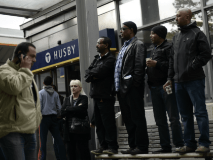 People stand on a street bench next to Husby subway station as they attend a demonstration against police violence and vandalism in the Stockholm suburb of Husby on May 22, 2013.