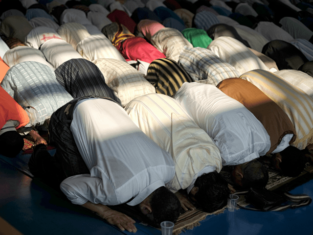 People pray during a celebration of Eid al-Fitr marking the end of the fasting month of Ramadan in Saluzzo, near Turin, on July 17, 2015. Muslims around the world are celebrating Eid al-Fitr this week, marking the end of the holy month of Ramadan during which followers are required to …