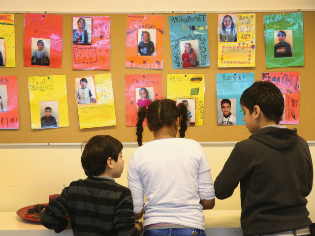 BERLIN, GERMANY - JANUARY 07: Children play under photographs of fellow pupils at the 'Welcome Class' for immigrant children, including children of migrants and refugees, at the Leo-Lionni-Schule primary school on January 7, 2016 in Berlin, Germany. Germany is investing in German language classes across the country by hiring more …