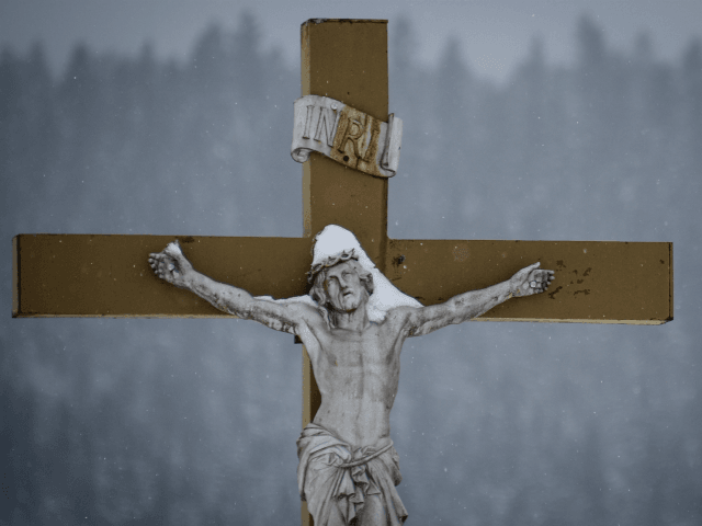 A picture taken on January 17, 2017 shows a snow-covered crucifix outside a church in the city of Mouthe, also dubbed 'Petite Siberie', renowned as the coldest town in France. The cold snap coming from Central Europe is generating temperatures of 5 to 10 degrees below the seasonal average, according …