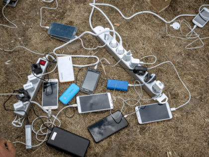 Migrants charge their mobile phones with a generator distributed by the international solidarity organisation Emmaus on May 12, 2017 in Grande-Synthe, northern France. Around 200 Iraqi Kurds live in a nearby forest, a month after the destruction of the migrant camp by a fire. / AFP PHOTO / PHILIPPE HUGUEN …