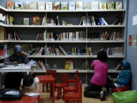 Refugees read books at a library set up on the premises of an international non-governmental organisation (NGO) hosting Syrian and Afghan women and children, in central Athens on August 17, 2017. There are increasingly initiatives in Greece to offer reading and books to the tens of thousands of refugees stranded …