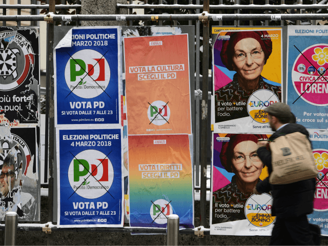 A pedestrian passes in front of election hoardings in Milan on March 1, 2018, prior to the Italian presidential elections. Growth up, deficit down: Italian Prime Minister Paolo Gentiloni's centre-left government got a boost from new data ahead of a weekend election in which the state of the economy is …