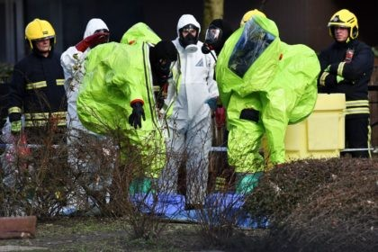Members of the fire brigade are helped out of their green biohazard suits by colleagues in white protective coveralls after an operation to re-attach the tent over the bench where a man and a woman were found in critical condition sparking a major incident on March 4 at The Maltings …