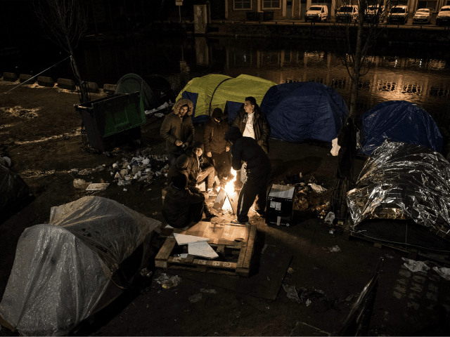 Migrants, mostly from Afghanistan, warm themselves up around a bonfire in freezing temperatures, by their tents at a makeshift camp set up along the canal Saint-Martin in Paris on March 19, 2018. / AFP PHOTO / CHRISTOPHE ARCHAMBAULT (Photo credit should read CHRISTOPHE ARCHAMBAULT/AFP/Getty Images)