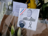 An image Lieutenant-Colonel Arnaud Beltrame is attached to a bouquet of flower laid outside the gates of the gendarmerie of Carcassonne where he worked in southwest France, on March 25, 2018, two days after a man carried out an attack in which he and three other people were killed. Lieutenant-Colonel …