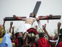 Ruben Enaje, 57, a Christian devotee reacts as he is nailed to a cross during a reenactment of the crucifixion of Jesus Christ during Good Friday celebrations ahead of Easter in the village of Cutud near San Fernando, north of Manila on March 30, 2018. / AFP PHOTO / NOEL …