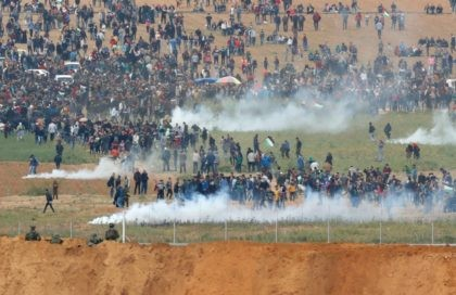 A picture taken on March 30, 2018 from the southern Israeli kibbutz of Nahal Oz across the border from the Gaza strip shows tear gas grenades falling during a Palestinian tent city protest commemorating Land Day, with Israeli soldiers seen below in the foreground. Land Day marks the killing of …