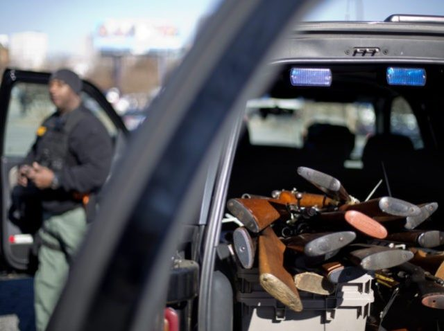 Rifles are piled up in the back of a Fulton County Sheriff's vehicle collected during a gun buyback, Thursday, Jan. 16, 2014, in Atlanta. The NAACP is looking to collect 1,000 firearms during the gun buyback which is part of NAACP programs centered on non-violence leading up to Martin Luther …