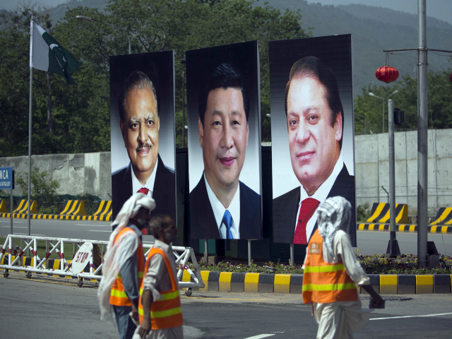 In this April 20, 2015 file photo, municipality workers walk past a billboard showing pictures of Chinese President Xi Jinping, center, with Pakistan's President Mamnoon Hussain, left, and Prime Minister Nawaz Sharif on display during a two-day visit by the Chinese president to launch an ambitious $45 billion economic corridor …