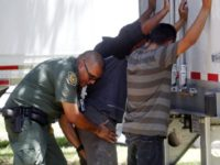 In this Sunday, Aug. 13, 2017, photo, a Border Patrol officer pats down several of the men that were found with a group of immigrants in a tractor-trailer in Edinburg, Texas. Police in Texas acting on a tip found the immigrants locked inside a tractor-trailer parked at a gas station …