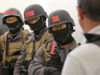 In this Sunday, March 18, 2018 photo, members of a Tunisian police commando unit listen to instructions during a drill at the Jordan Gendarmerie Training Academy, in al-Swaqa, about 44 miles (70 km) south of Amman, Jordan. The U.S.-funded center, which formally opens Thursday, will conduct counter-terrorism training for law enforcement agencies from a pool of 56 eligible partner countries. (AP Photo/Raad Adayleh)