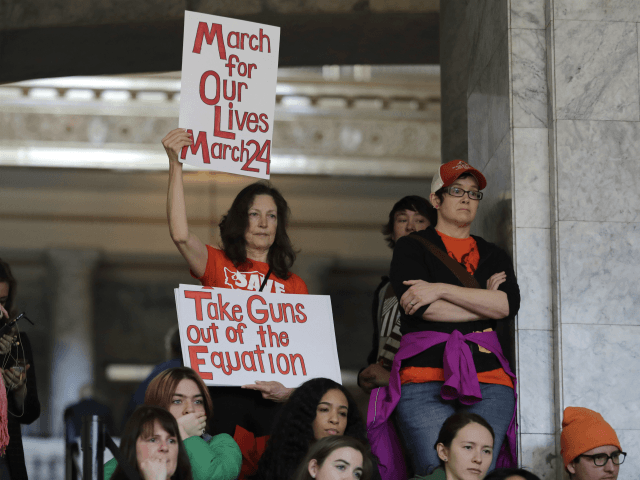 "An attendee at a rally against gun violence holds signs that read ""March for Our Lives March 24"" and ""Take Guns Out of the Equation,"" Tuesday, March 6, 2018, at the Capitol in Olympia, Wash. The rally was held on the same day Gov. Inslee was scheduled to sign a …"