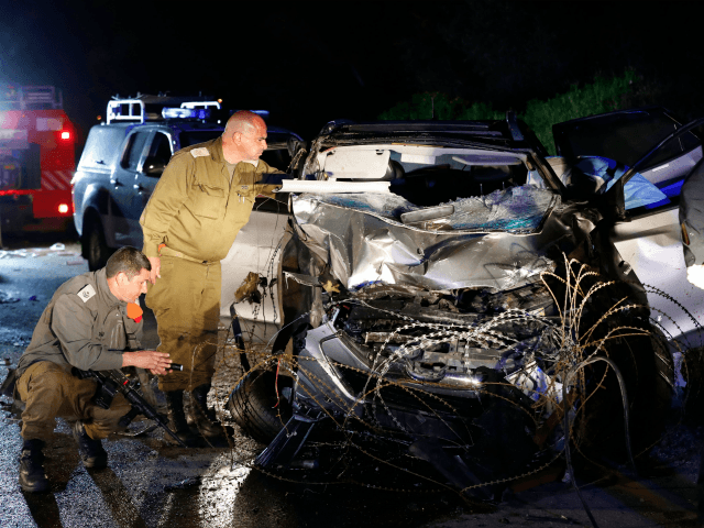 Israeli security forces and forensics inspect the destroyed vehicle that was used by a Palestinian assailant in a car ramming attack targeting a group of Israeli soldiers near Mevo Dotan in the north of the occupied West Bank on March 16, 2018. / AFP PHOTO / Jack GUEZ (Photo credit …