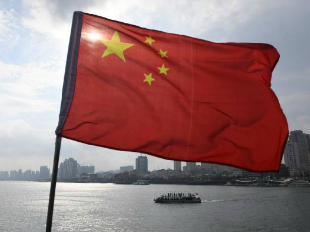 A Chinese tour boat cruises on the Yalu River behind the Chinese flag flying on the Broken Bridge, in the border city of Dandong, in China's northeast Liaoning province on September 5, 2017. The Broken Bridge once connected Dandong and the North Korean town of Sinuiju, but was bombed by …