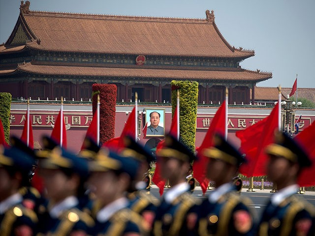 The portrait of late communist leader Mao Zedong is seen behind a Chinese military honour guard as they wait for the start of a welcome ceremony for Cambodia's Prime Minister Hun Sen outside the Great Hall of the People in Beijing on May 16, 2017. Hun Sen is on a …
