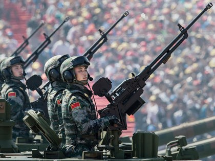 BEIJING, CHINA - SEPTEMBER 03: Chinese soldiers ride in an armoured vehicle as they hold machine guns while passing in front of Tiananmen Square and the Forbidden City during a military parade on September 3, 2015 in Beijing, China. China is marking the 70th anniversary of the end of World …