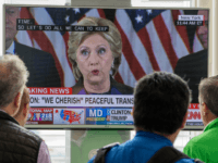 People walking at Ronald Reagan National Airport airport gather around a television monitor and watch US Democratic nominee Hillary Clinton deliver her concession speech November 9, 2016, a day following the election that US Republican nominee Donald Trump won in Arlington, Virginia. / AFP / PAUL J. RICHARDS (Photo credit …