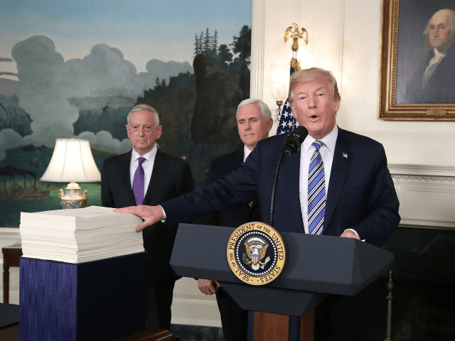 WASHINGTON, DC - MARCH 23: U.S. President Donald Trump gestures to the $1.3 trillion spending bill passed by Congress early Friday, with Vice President Mike Pence (C), and Defense Secretary Jim Mattis (L), in the Diplomatic Room of the White House on March 23, 2018 in Washington, DC. After threatening …