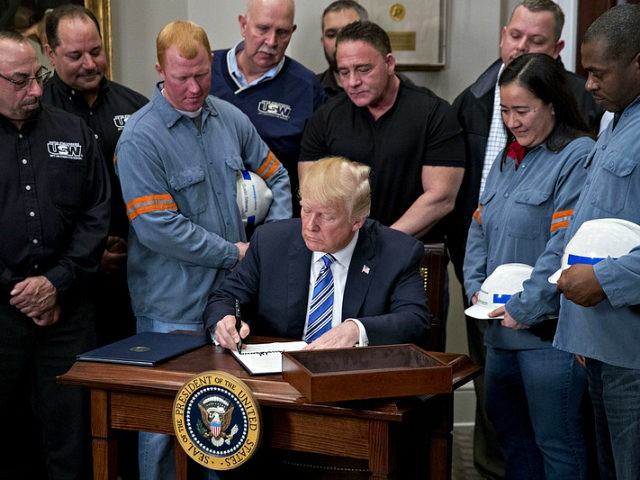 U.S. President Donald Trump signs a proclamation on adjusting imports of steel into the United States next to steel and aluminum workers in the Roosevelt Room of the White House in Washington, D.C., U.S., on Thursday, March 8, 2018. Trump signed the order over steel and aluminum tariffs that he …