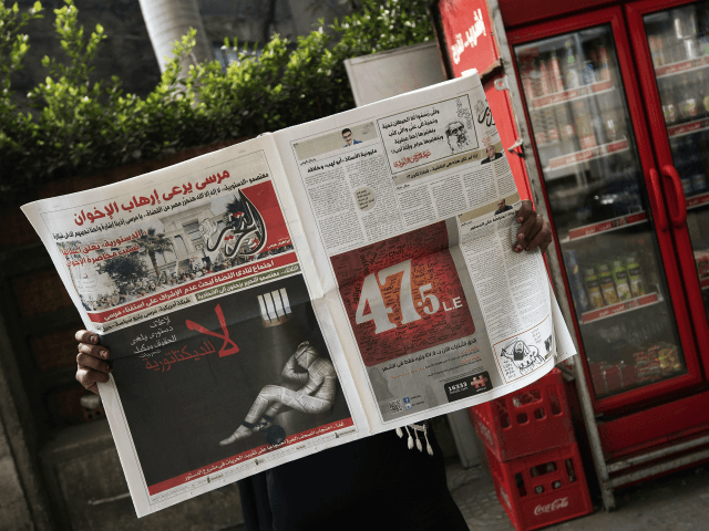 A woman reads a copy of Egyptian newspaper 'Al-Tahrir' with the headline 'No to Dictatorship' on December 3, 2012 in Cairo. A cartoon of a newspaper in human form chained in a cell was pasted on the front of several independent papers including Al-Watan and Al-Masry Al-Youm with the line …