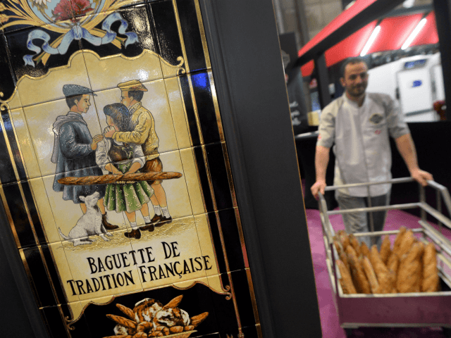 A man carries a cart full of baguettes as a sign reads 'French traditionnal baguette' during Europain 2014, a World Bakery, Patisserie and Catering exhibition held in Villepinte, north of Paris, on March 9, 2014. AFP PHOTO / PIERRE ANDRIEU (Photo credit should read PIERRE ANDRIEU/AFP/Getty Images)