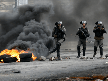 Israeli border guards walk through fumes from burning tires during clashes with Palestinian protesters near the Israeli settlement of Beit El in the Israeli occupied West Bank, on March 30, 2018, after Land Day demonstrations. Land Day marks the killing of six Arab Israelis during 1976 demonstrations against Israeli confiscations …