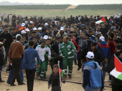 Palestinian medics carry a wounded man who was shot by Israeli troops during a demonstration near the Gaza Strip border with Israel, in eastern Gaza City, Friday, March 30, 2018. (AP Photo/ Khalil Hamra)