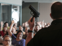 Firearm instructor Clark Aposhian holds a handgun up as he teaches a concealed-weapons training class to 200 Utah teachers on December 27, 2012 in West Valley City, Utah. The Utah Shooting Sports Council said it would waive its $50 fee for concealed-weapons training for Utah teachers. (Photo by George Frey/Getty Images)