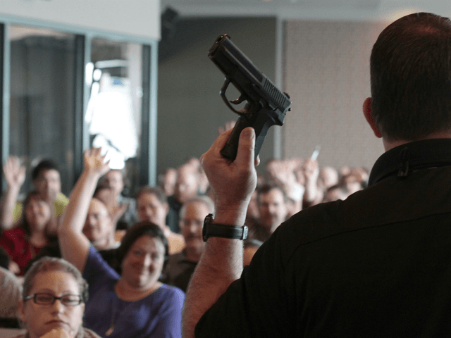 Firearm instructor Clark Aposhian holds a handgun up as he teaches a concealed-weapons training class to 200 Utah teachers on December 27, 2012 in West Valley City, Utah. The Utah Shooting Sports Council said it would waive its $50 fee for concealed-weapons training for Utah teachers. (Photo by George Frey/Getty …
