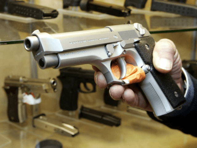 A shop attendant holds a pistol at a guns shop in Naples, southern Italy, Tuesday, Jan. 24, 2006. Provoking protests, Italian lawmakers Tuesday approved a self-defense bill allowing citizens to use guns and other weapons to protect their property at home or at work as well as to save their …