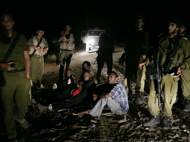In this Aug. 20, 2007 file photo, a Sudanese refugee family sit on the ground surrounded by Israeli army soldiers after they crossed illegally from Egypt into Israel. The Israeli Cabinet voted unanimously Sunday, Dec. 11, 2011, to finance a $160 million program designed to staunch the flow of illegal …
