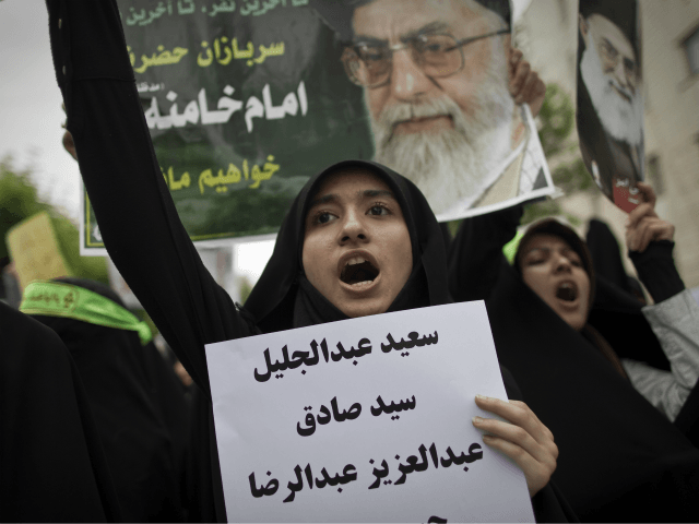 An Iranian hard line student chants as she holds the names of Bahraini Shiite Muslim protesters who were sentenced to death and life in prison by Bahraini military court outside the Bahrain embassy in Tehran on April 30, 2011, during a protest to commemorate the people who were killed in …