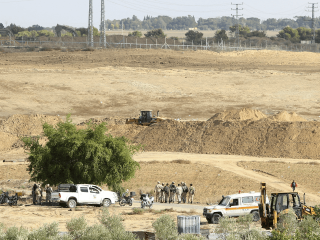 Hamas security forces secure the area while Palestinian bulldozers, at foreground, and Israeli backhoes, at midground, search the destroyed tunnel for the missing of five Islamic Jihad militants near the Israeli border east of Khan Younis, Gaza Strip, Friday, Nov. 3, 2017. The Islamic Jihad, says five of its members …