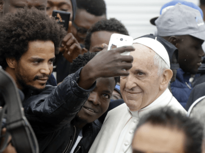 In this Oct. 1, 2017 file photo, Pope Francis poses for selfies with migrants at a regional migrant center, in Bologna, Italy. In a message issued by the Vatican Friday, Nov. 24, 2017, Francis is decrying those whipping up fear of migrants for political gain, and is urging people to …