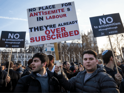 Protesters hold placards as they demonstrate in Parliament Square against anti-Semitism in the Labour Party on March 26, 2018 in London, England. The Board of Deputies of British Jews and the Jewish Leadership Council have drawn up a letter accusing Labour Leader Jeremy Corbyn of failing to address anti-Semitism in …