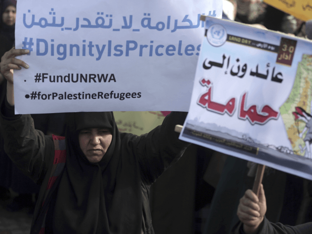 """Thousands of employees of the U.N agency for Palestinian refugees demonstrate in support of their organization following U.S. funding cuts in Gaza City, Monday, Jan. 29, 2018. Earlier this month, the Trump administration slashed $60 million of a planned $125 million funding installment for 2018. Washington wants the Palestinian Authority to return to the negotiating table with Israel in exchange for aid resumption. Arabic at right reads """"Returning to Hamama village."""" (AP Photo/ Khalil Hamra)"""