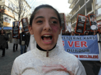 A Turkish girl, wearing a wedding dress and covered with fake bruises, shouts in front of other protesters holding placard reading '' end violence'' during a demonstration to protest against rape, killings and domestic violence against women, in Ankara on November 27, 2011. AFP PHOTO/ADEM ALTAN (Photo credit should read …